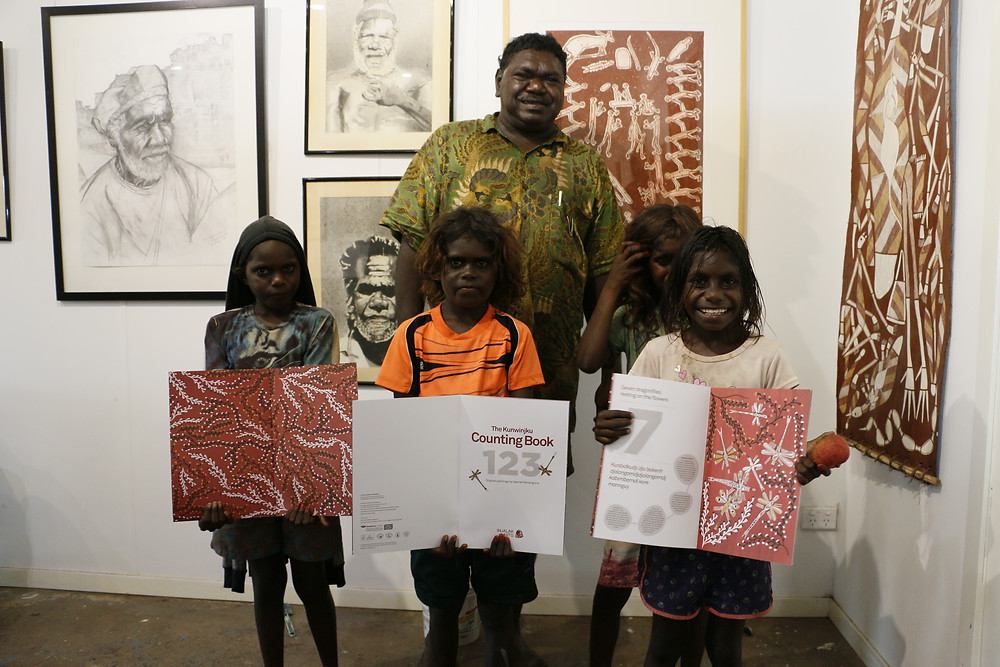 Aboriginal children with Kunwinjku Counting Book at Gunbalayna at Injalak Art Centre
