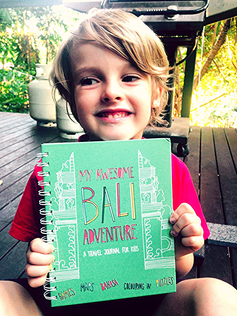Little boy with childrens travel guide to Bali