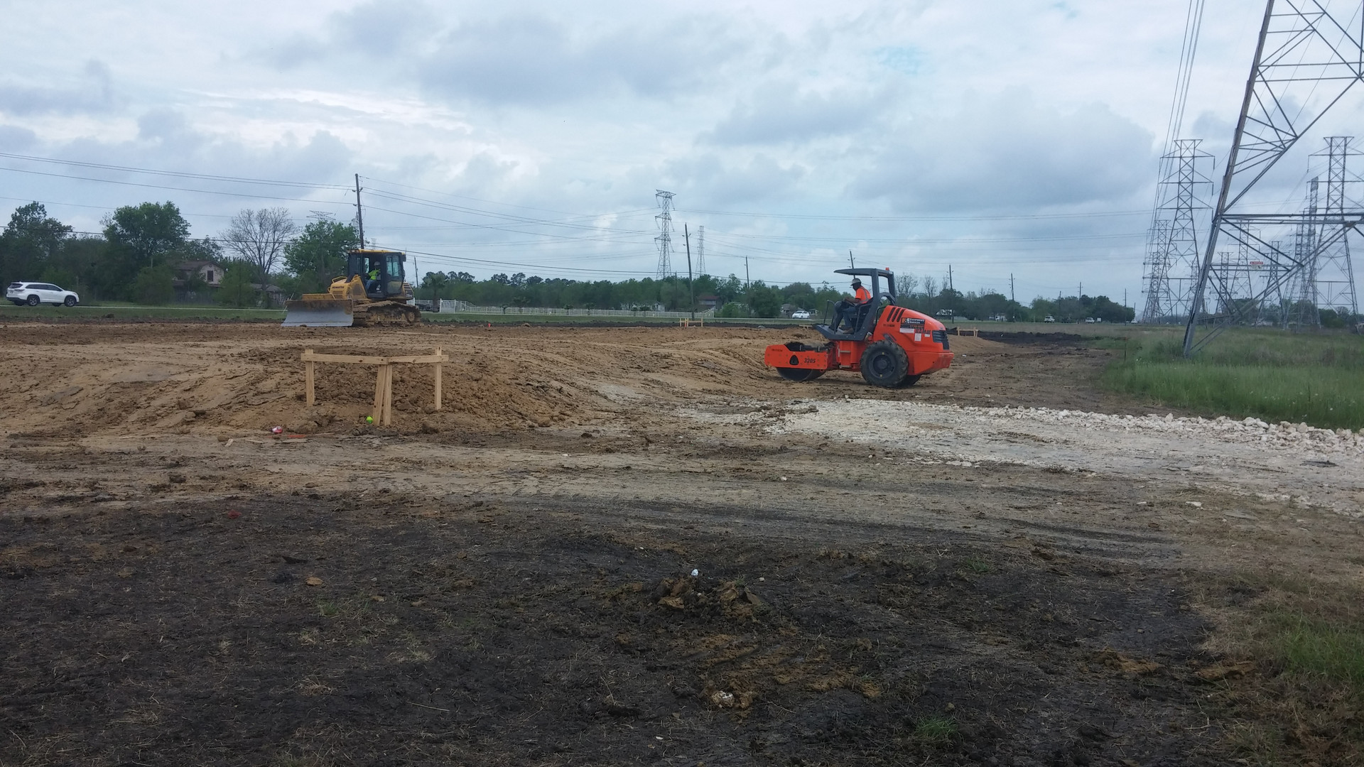 pad site with roller and dozer in distance