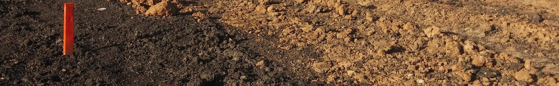 Black mulch and tilled brown dirt ground