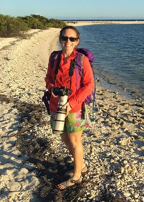 Jenny Howard standing on a beach with camera in hand