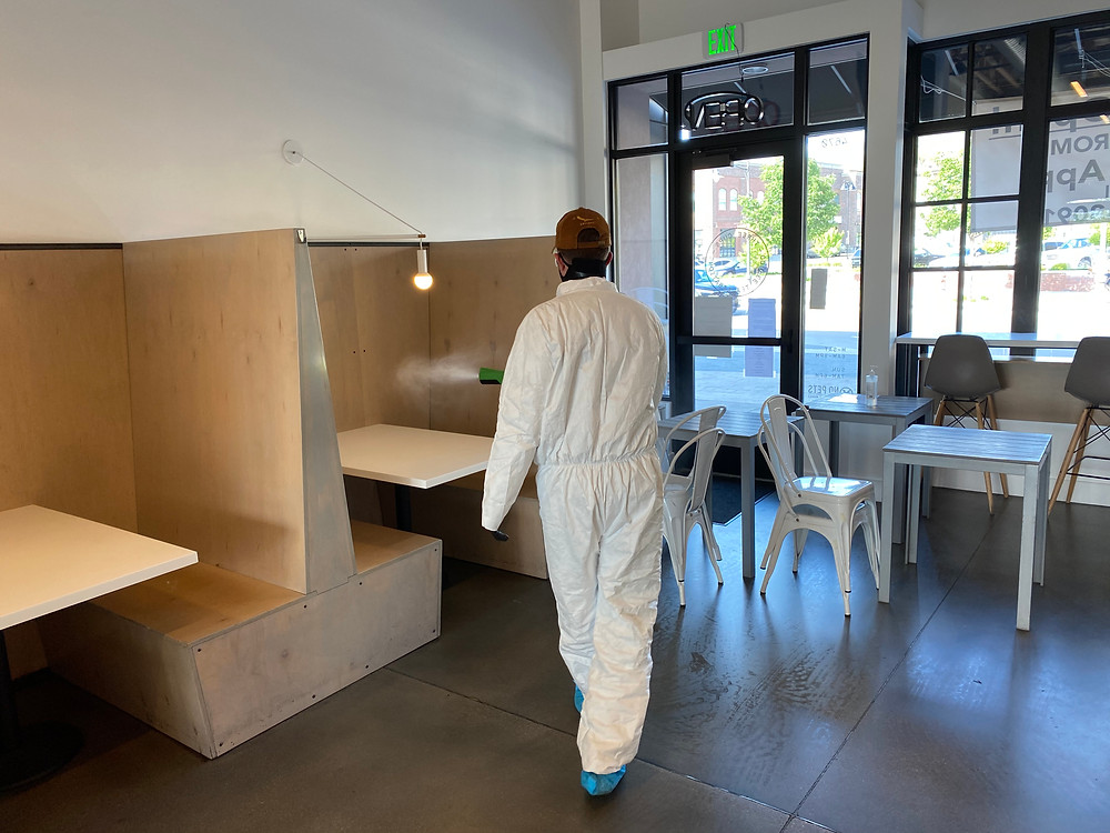 Sanilast technician applying sanitizer with an electrostatic sprayer on restaurant booths..
