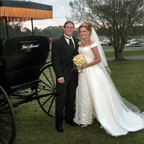 Bride and groom next to antique surrey at Azalee Plantation