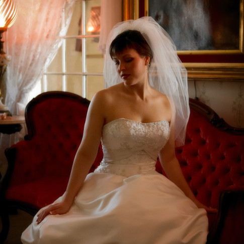 Classic bride on antique sofa in parlor at Azalee Plantation
