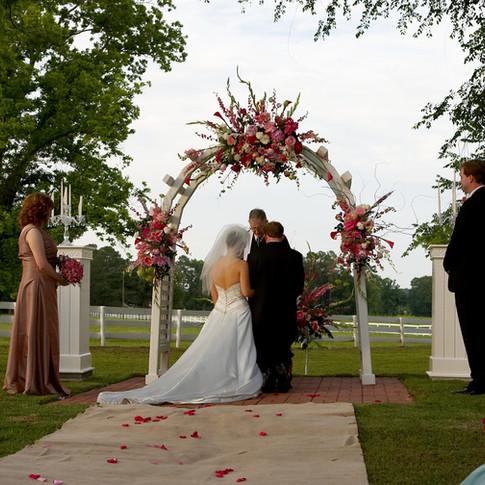 Bride and groom under floral wedding arch at Azalee Plantation