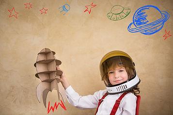 Kid astronaut with cardboard toy rocket.