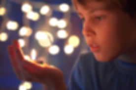 boy holds in a hand a burning candle aga