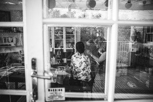 Black and white image through window at bridal prep photographed by de lumière photography