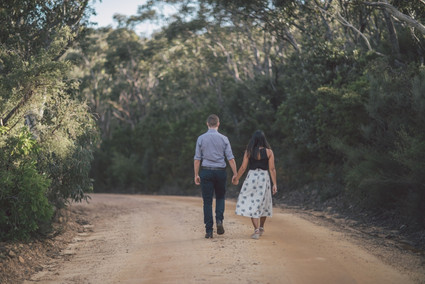 Couple holding hands walking down road
