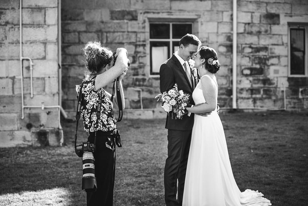Sarah Moore owner of de lumière photography photographing the bride and groom