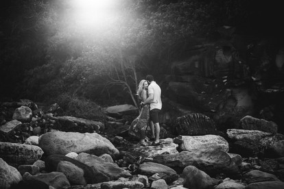 The engaged couple hugging on rocks at Little Bay with Sydney Wedding Photographers de lumière photography