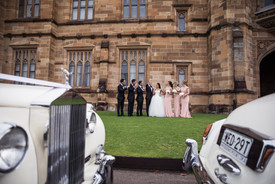 the bridal party framed between the roll up in a rolls wedding cars