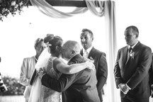 Dad kisses his daughter at the end of the aisle - de lumière photography