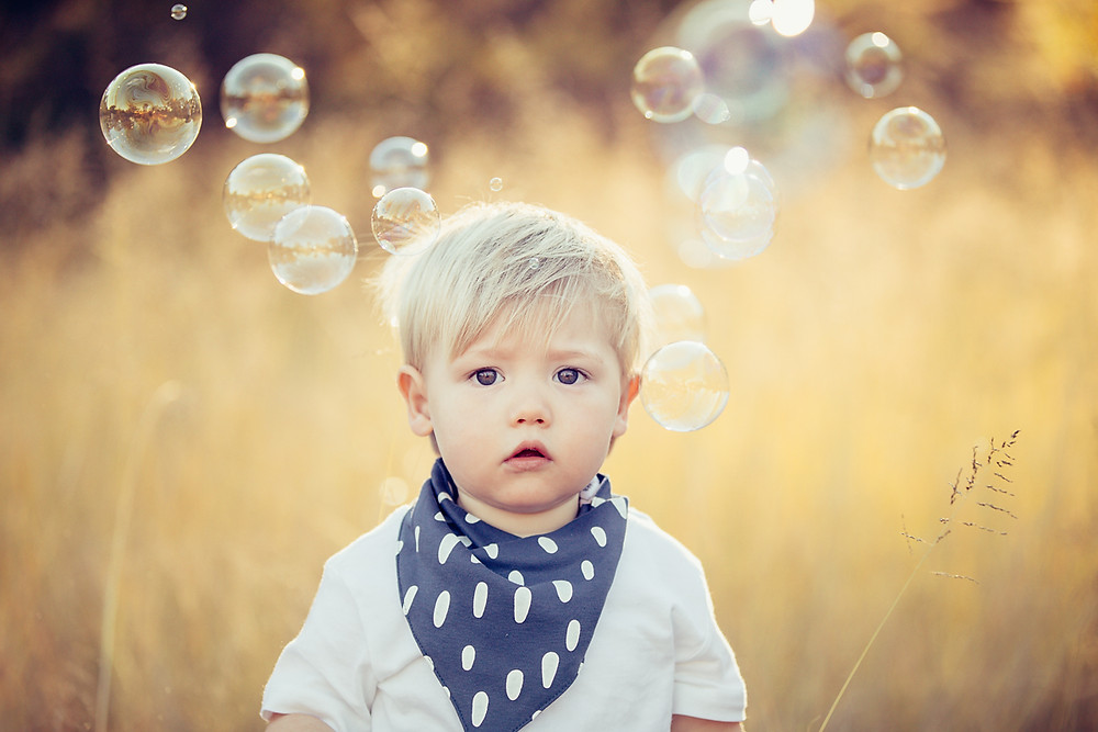 Child with bubbles photographed by de lumière photography
