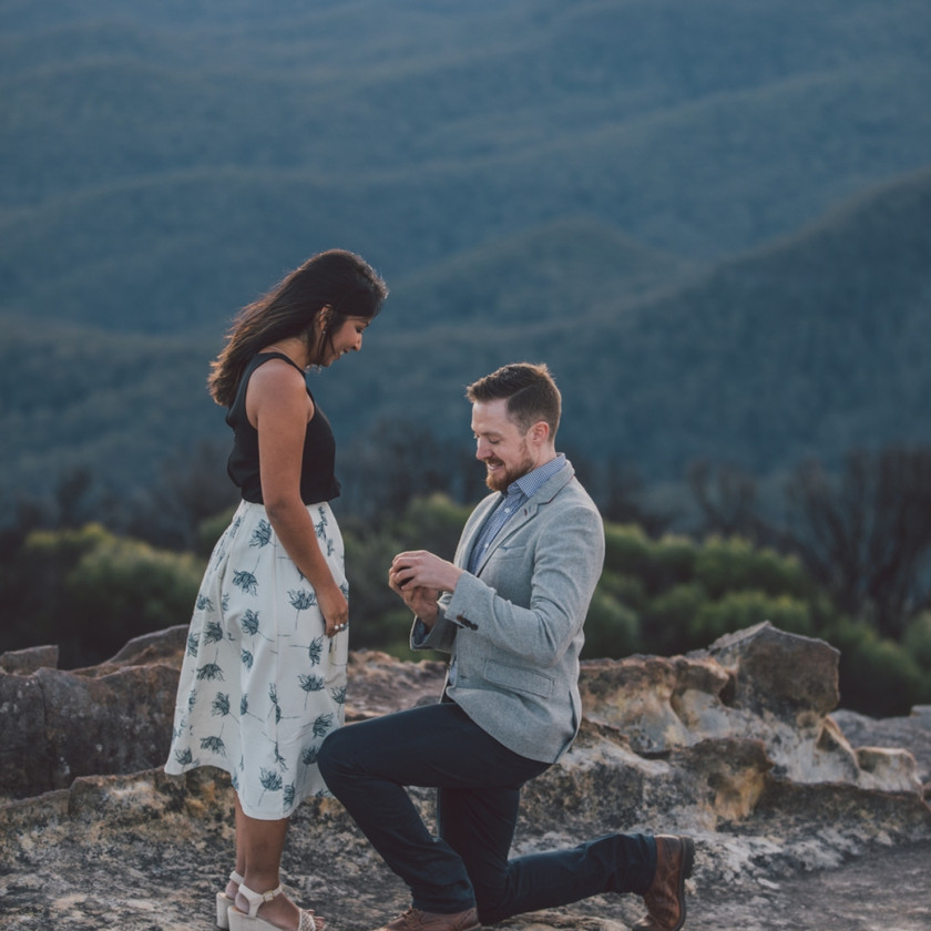 Man gets down on one knee with ring box