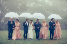 Gorgeous bridal party taking a walk in the rain and laughing - de lumière photography