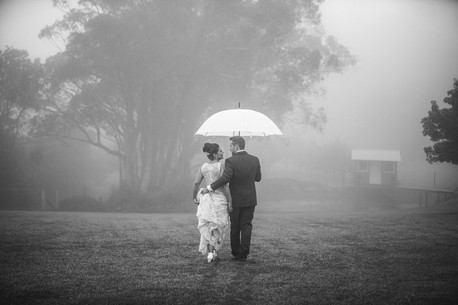 Misty wedding day with lake - bride and groom walk under umbrella - de lumière photography