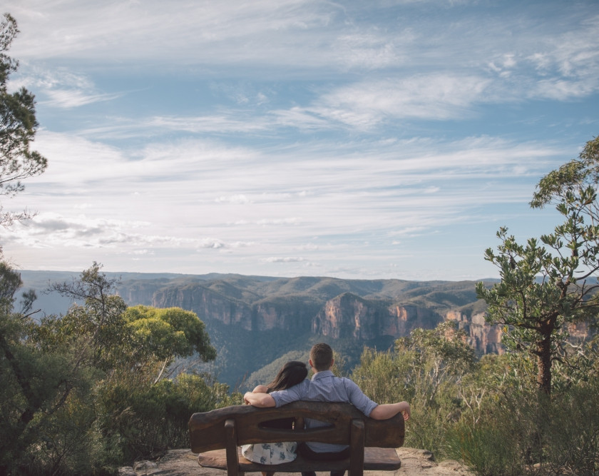 Couple sitting on seat looking out over valley