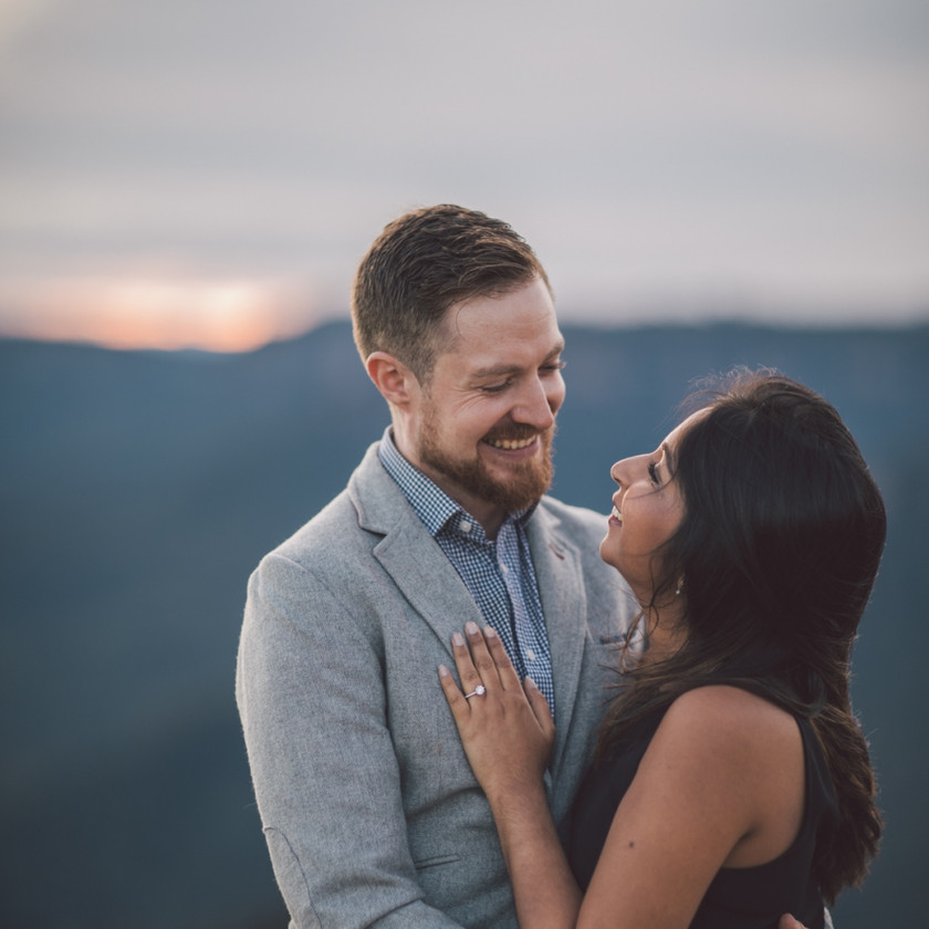 Man and woman smiling with engagement ring