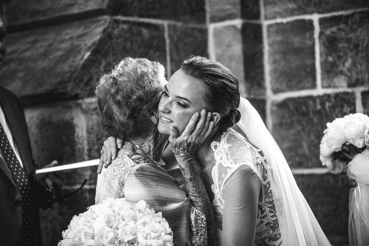 Grandmother hugs her grand-daughter after the wedding ceremony photographed by de lumière photography