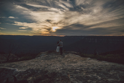 Couple hugging with sun going down over the mountains