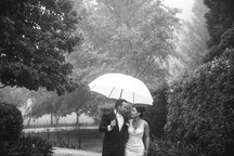 Rainy wedding day with bride and groom walking together holding umbrella
