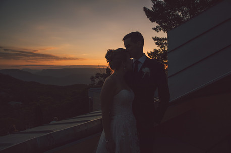 bride and groom at sunset over blue mountains