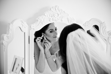 bride putting on earrings in mirror