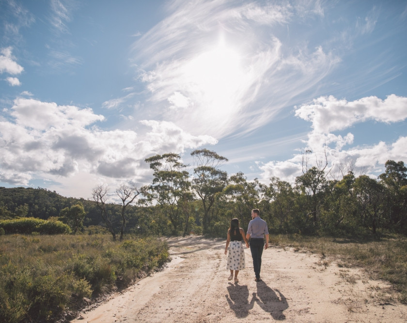 Gorgeous clouds with couple walking along a dirt road