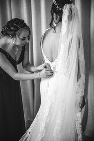 Bridesmaid doing up bride's gown country wedding photographer