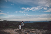 Woman and man walking over rock