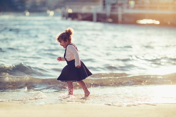 Young girl running in the ocean