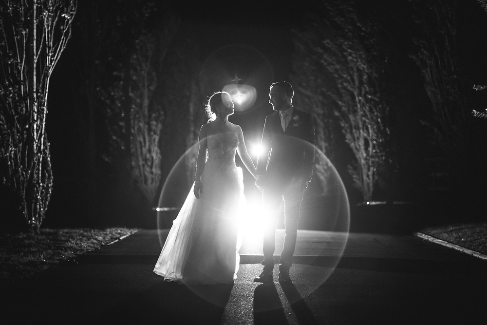 Black and white image of couple walking at night, Bendooley Estate