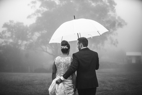 Groom assisting bride and holding an umbrella on raingy wedding day - de lumière photography