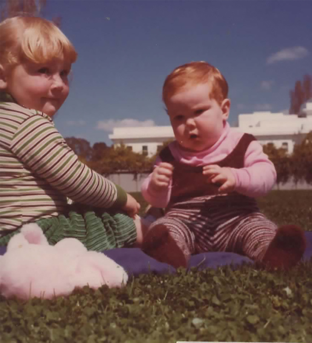 1970s image of two children sitting on grass