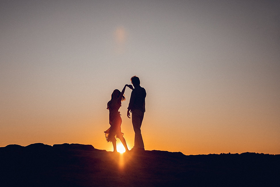 engaged couple dancing under a blue mountains sunset
