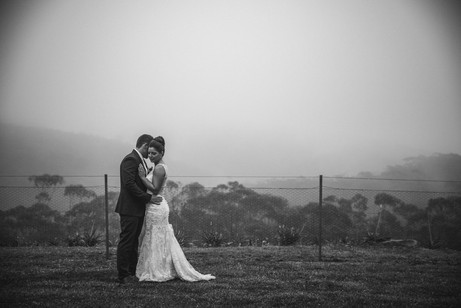 Bride and groom standing in the mist on their mountains wedding day - de lumière photography