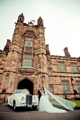 bride and groom with roll up in a rolls wedding cars at sydney university