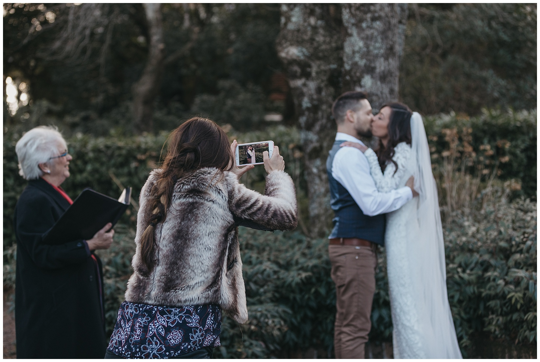 Guest taking photos of the bride and groom on her iphone