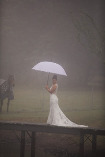 Bride standing under an umbrella in the rain with a horse in the background - de lumière photography
