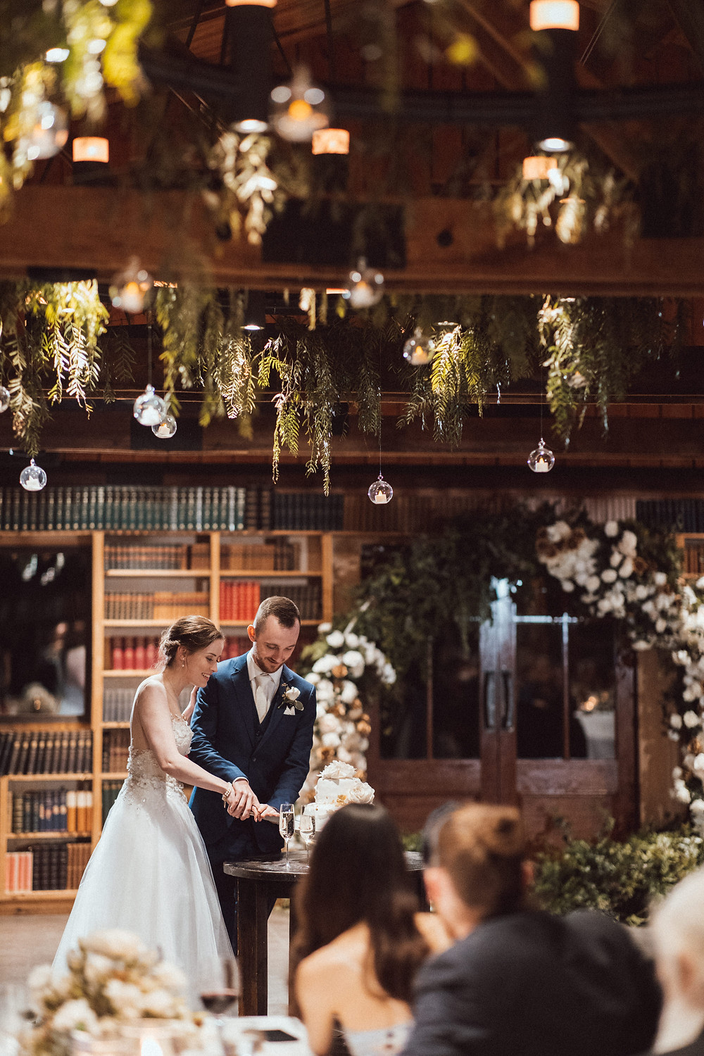 Bride and groom cutting the cake in the Book Barn at Bendooley Estate