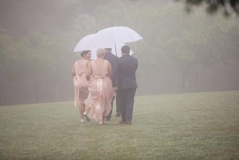 Bridal party under umbrellas in the rain - de lumière photography