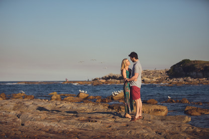 Newly engaged couple hugging at beach with seagulls and ocean in the background captured by Sydney Wedding Photographers de lumière photography