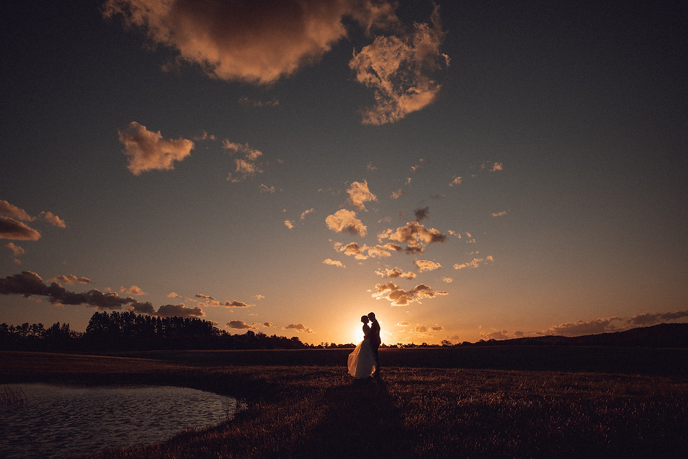 bride and groom embrace against sunset sky bendooley estate destination wedding venue