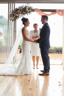 The bride and groom exchange vows during the ceremony by Blue Mountains Wedding Photographers de lumière photography
