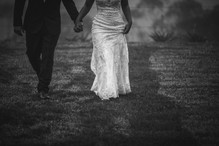 Black and white images of the bride and groom walking through wet grass - de lumière photography