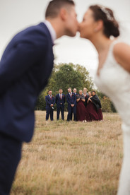 bride and groom kiss with bridal party in background country wedding de lumiere photography