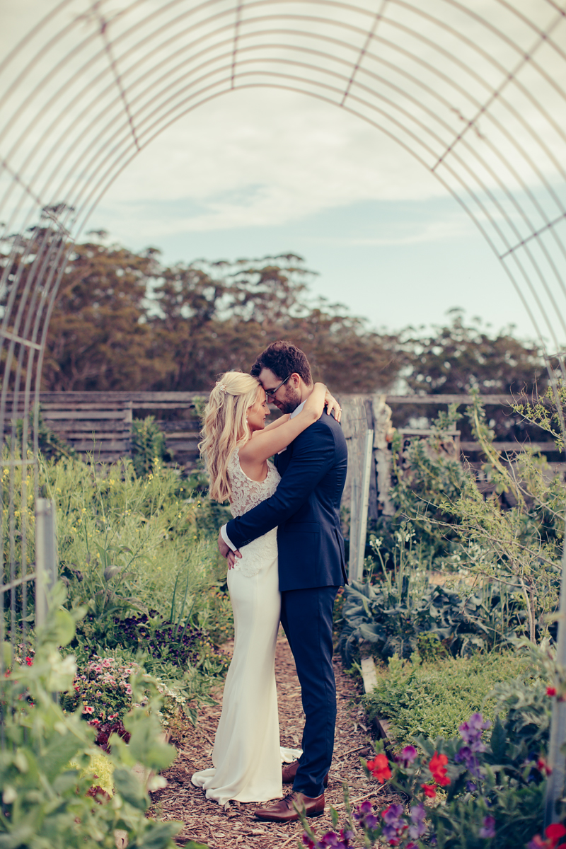 Bride and groom share a hug in veggie garden