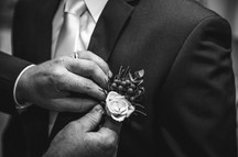 Father of the groom pinning on the groom's corsage photographed by de lumière photography