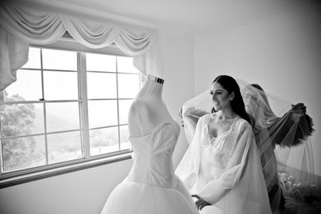 black and white photo of bride admiring her vera wang wedding dress